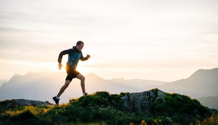 young man running on mountain ridge at sunrise